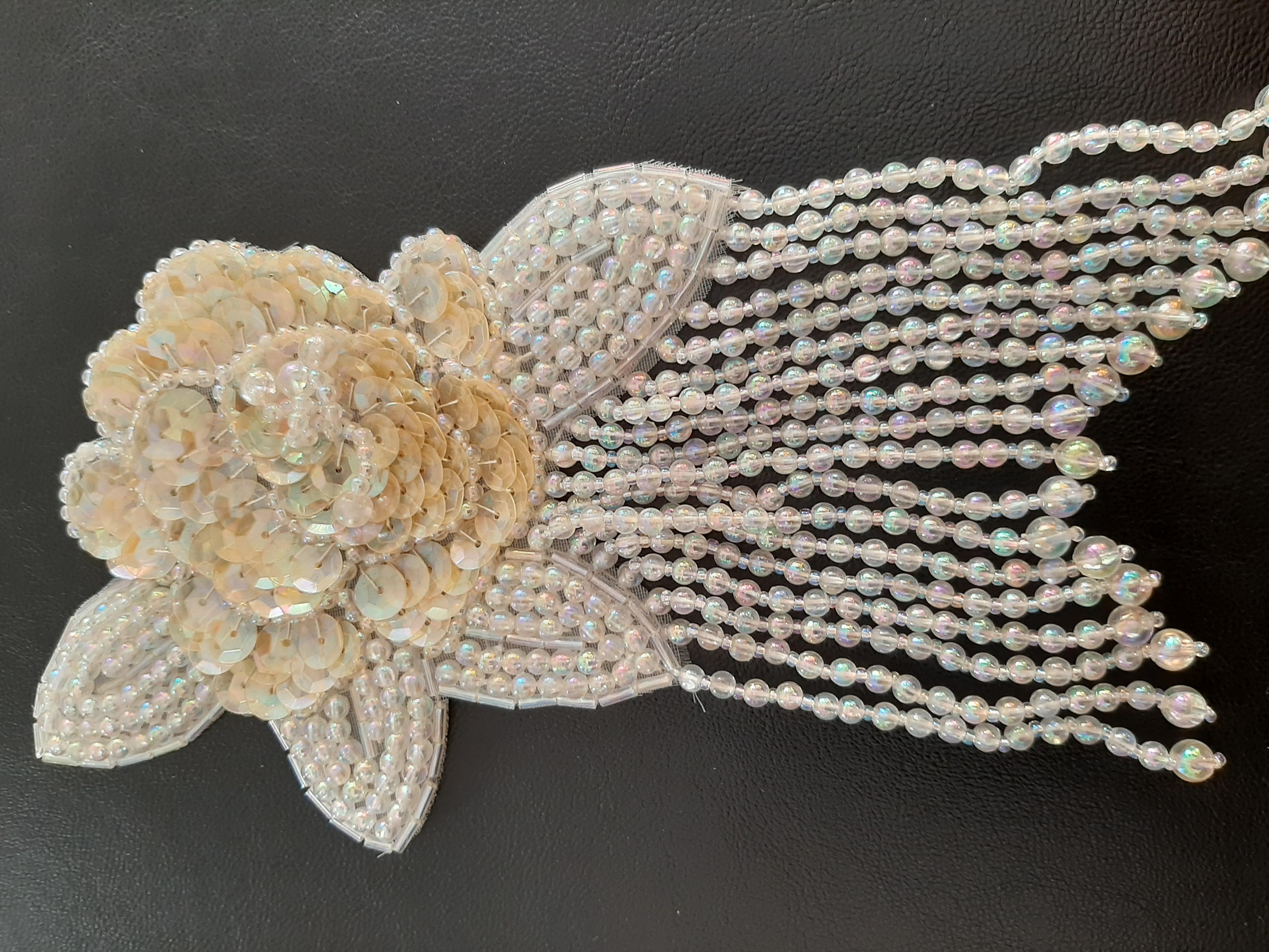 Applikation  mit  schillernde Perlen  und gelbliche  Pailletten